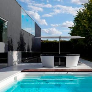 Ambiente con Kosmos asientos bajos y mesa fija color negro y parasol Inumbrina de Extremis, disponible en Moisés showroom